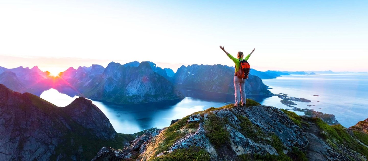 Male tourist holding hands up on top on mountain